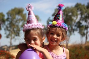 Naming Ceremonies tailored to your family.  2 girls in party hats