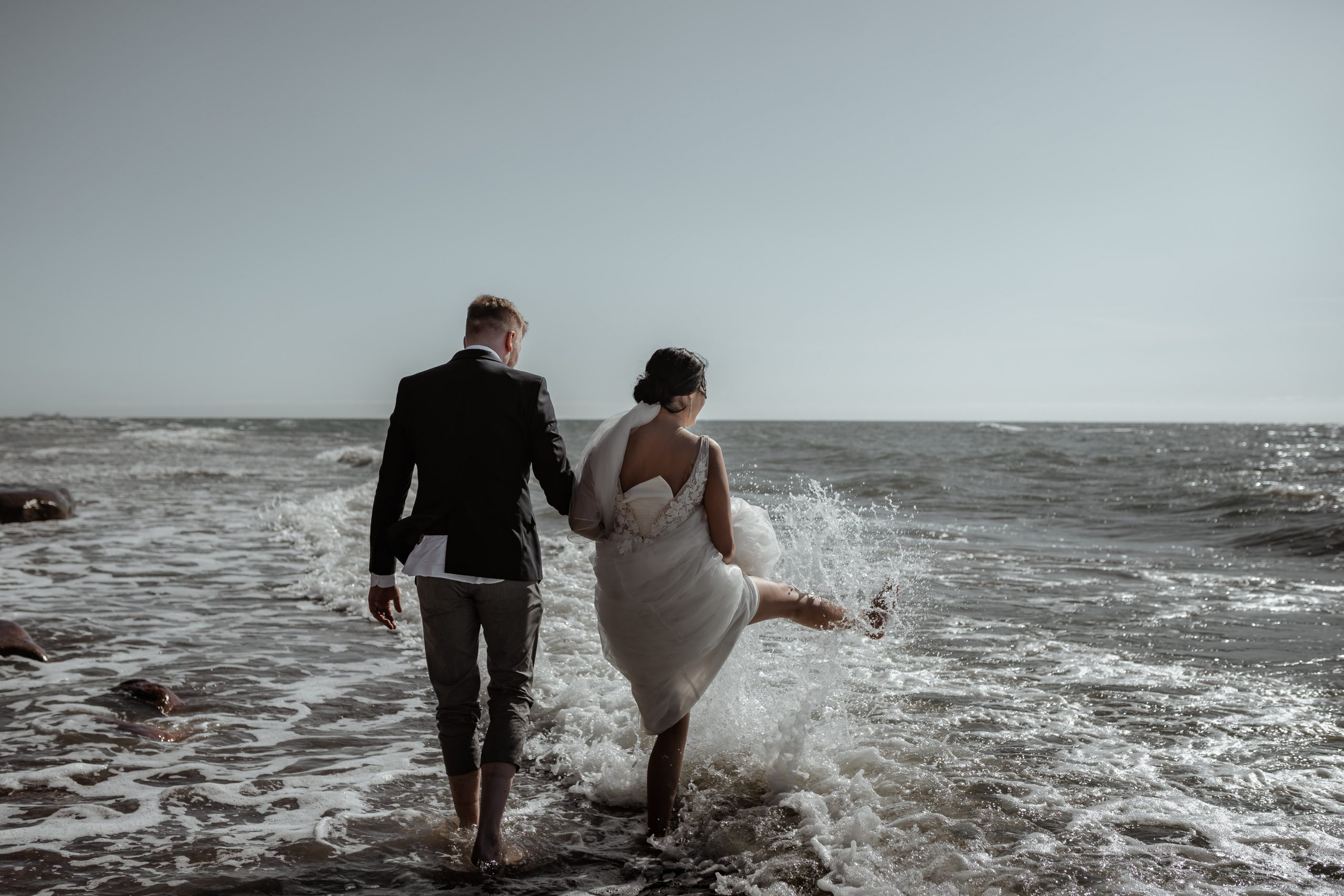 Bride and Groom paddling in the sea