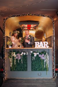 bride and groom drinking cocktails in a beautiful horse-box bar