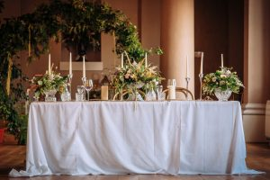 The bride and grooms table dressed in peach flowers and greenery with lots of cut-glass and candles
