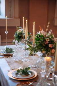 table dressed with crystal cut-glass, tall glass candlesticks and lots of greenery and flowers