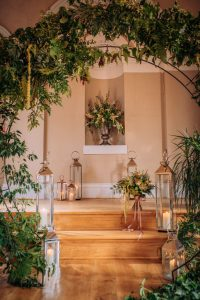 wedding ceremony area dressed with flowers, greenery and storm lanterns