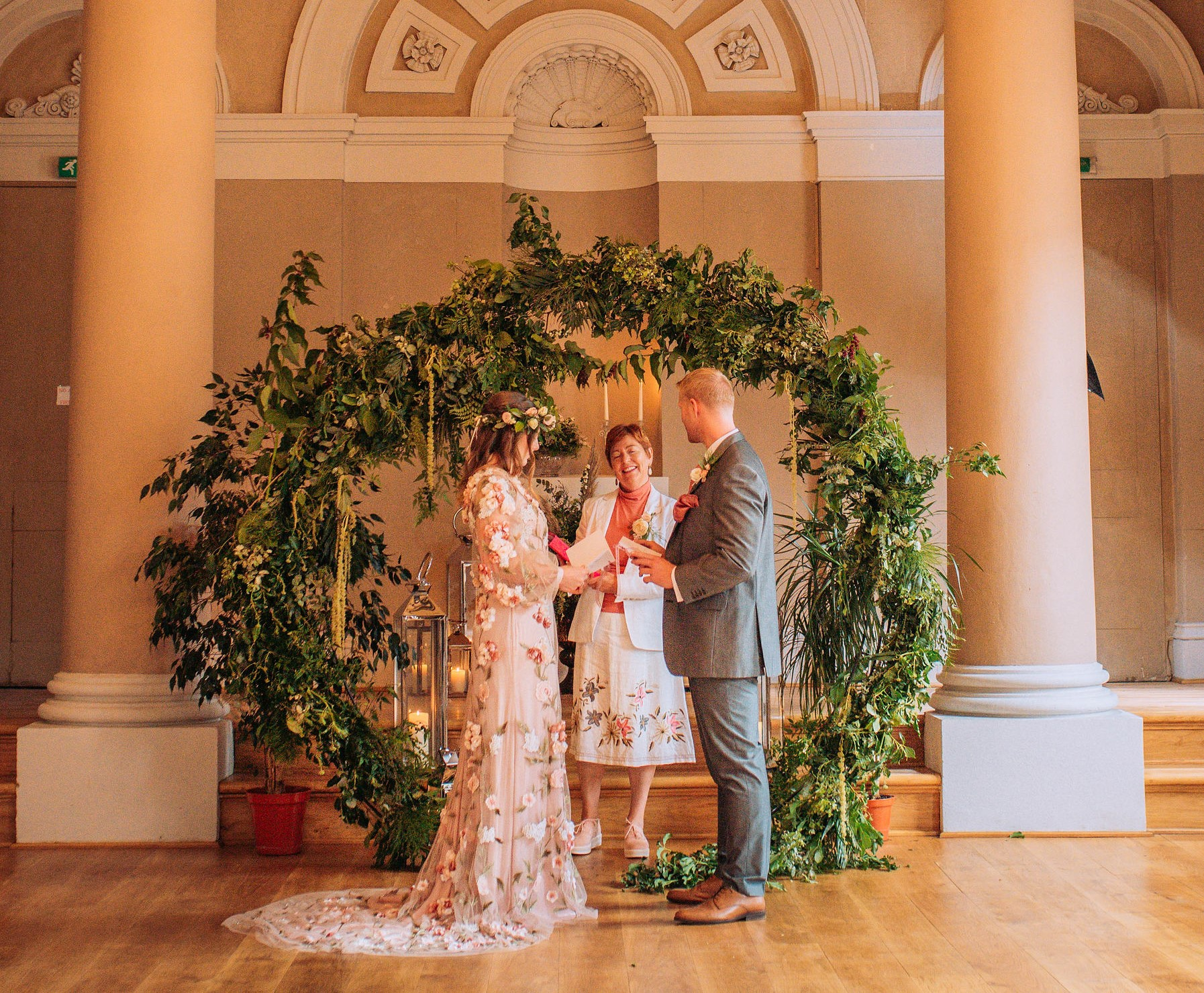 Bride and Groom exchanging their Wedding Vows. With Wedding Officiant and a Ceremony area dressed in greenery