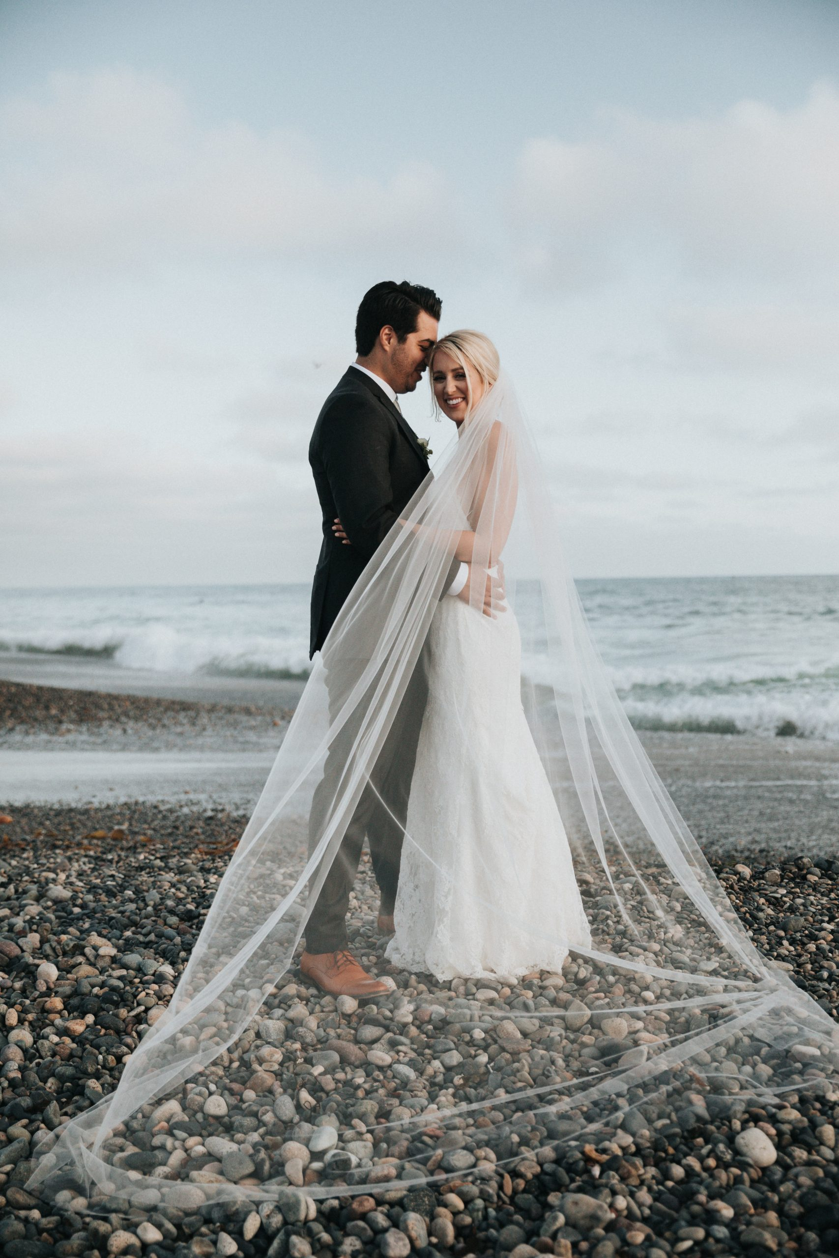 bride and groom on a pebble beach