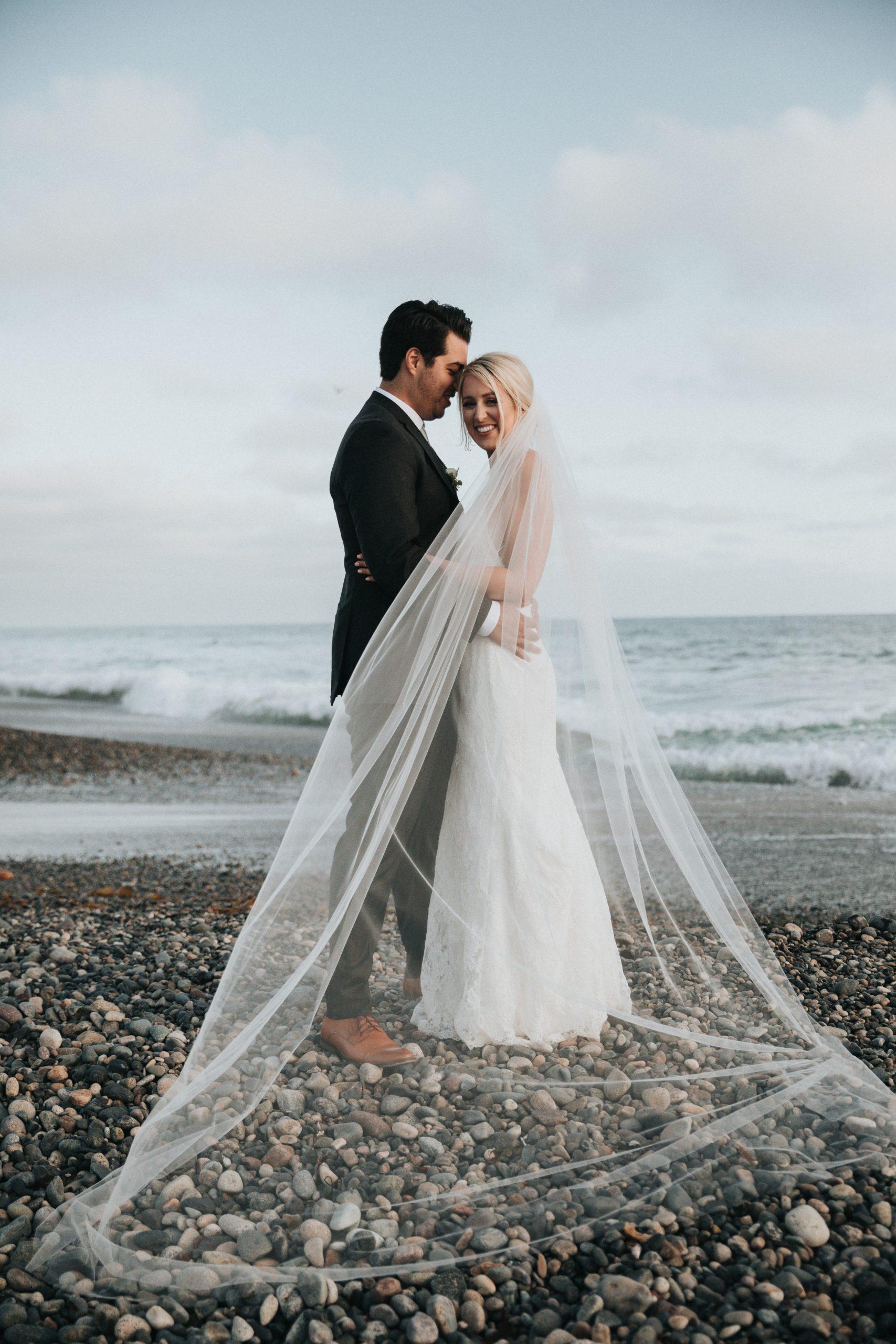 bride and groom on a pebble beach
