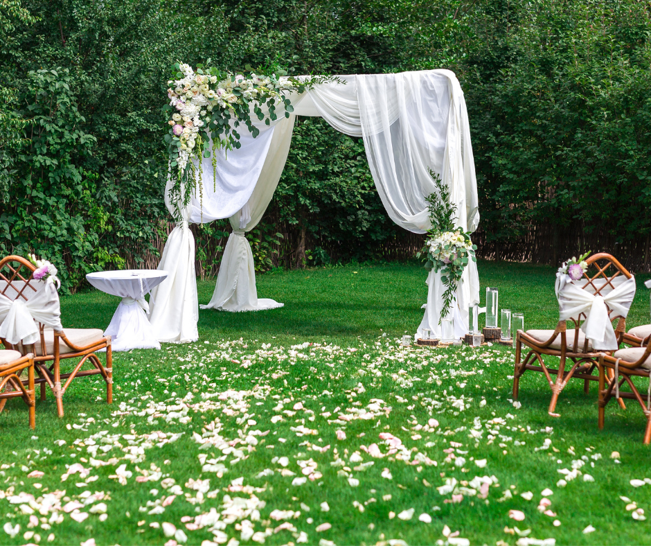 garden lawn area set up for a wedding ceremony.  Chairs decorated with white fabric and a ceremony area draped with floaty white fabric and white flowers.  On the grassy aisle white flowers are strewn