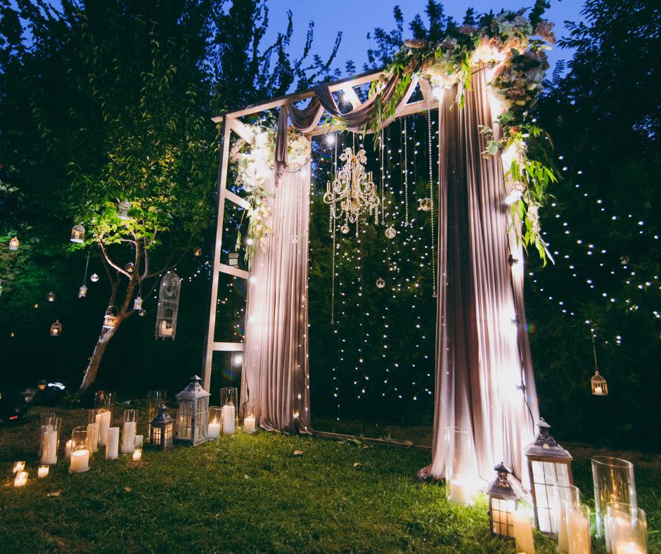 Wedding Ceremony Backdrop. A wooden framework draped with floaty material and lights and surrounding by candles and lanterns