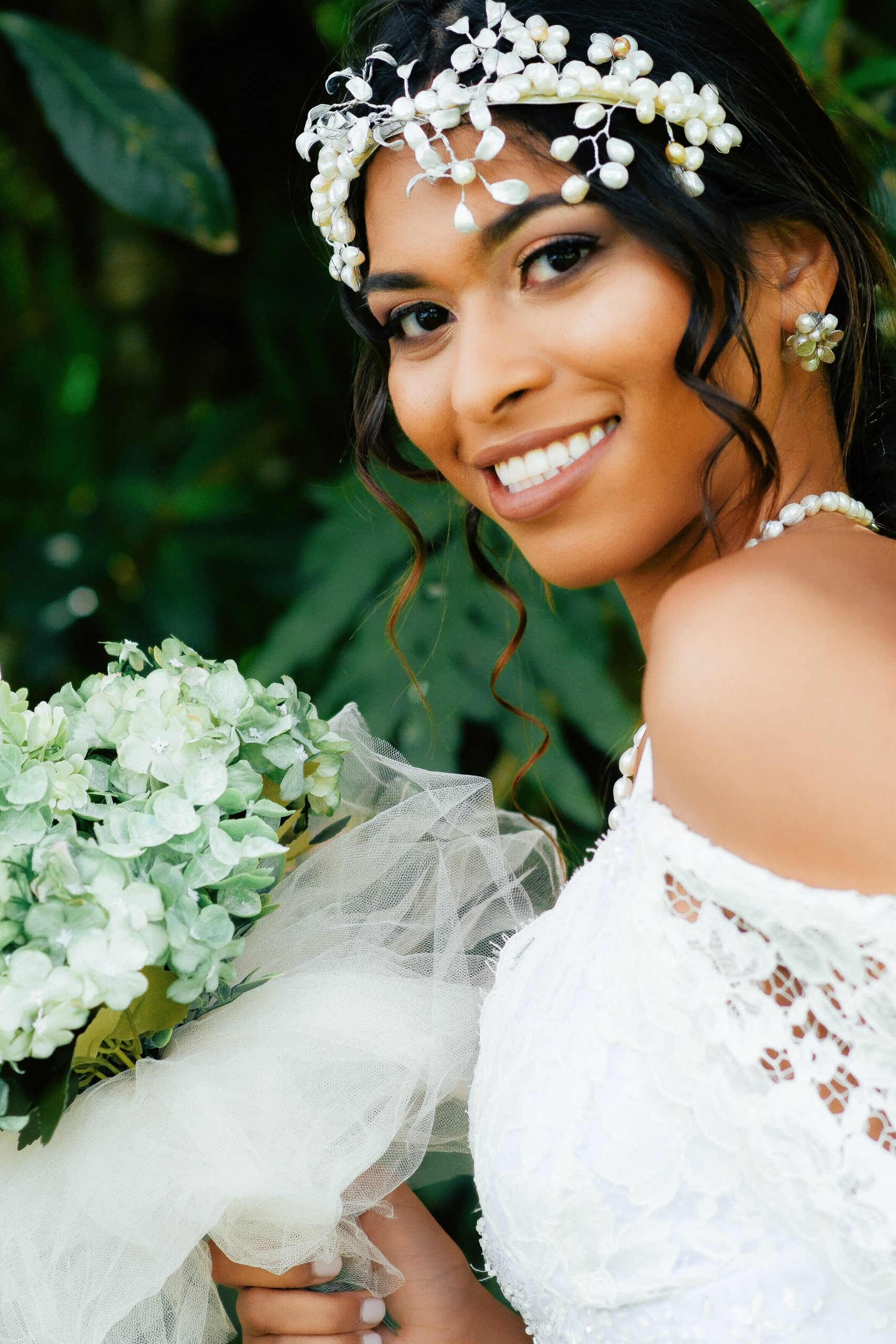 bride with a headdress and holding a white bouquet smiling at the camera