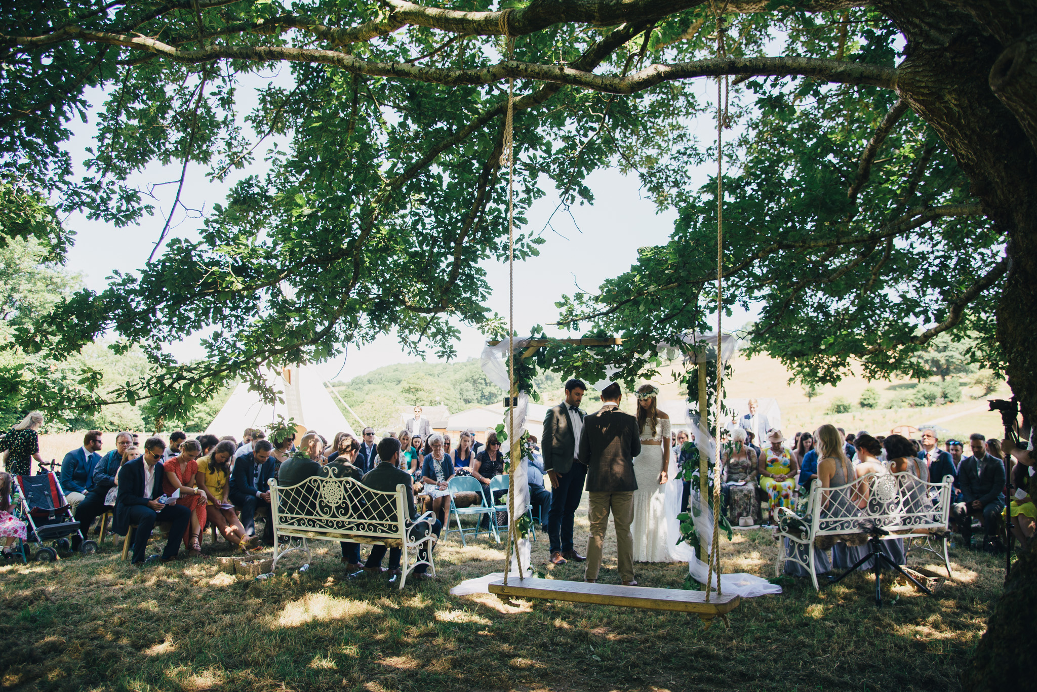 An outdoor wedding ceremony under an ancient tree
