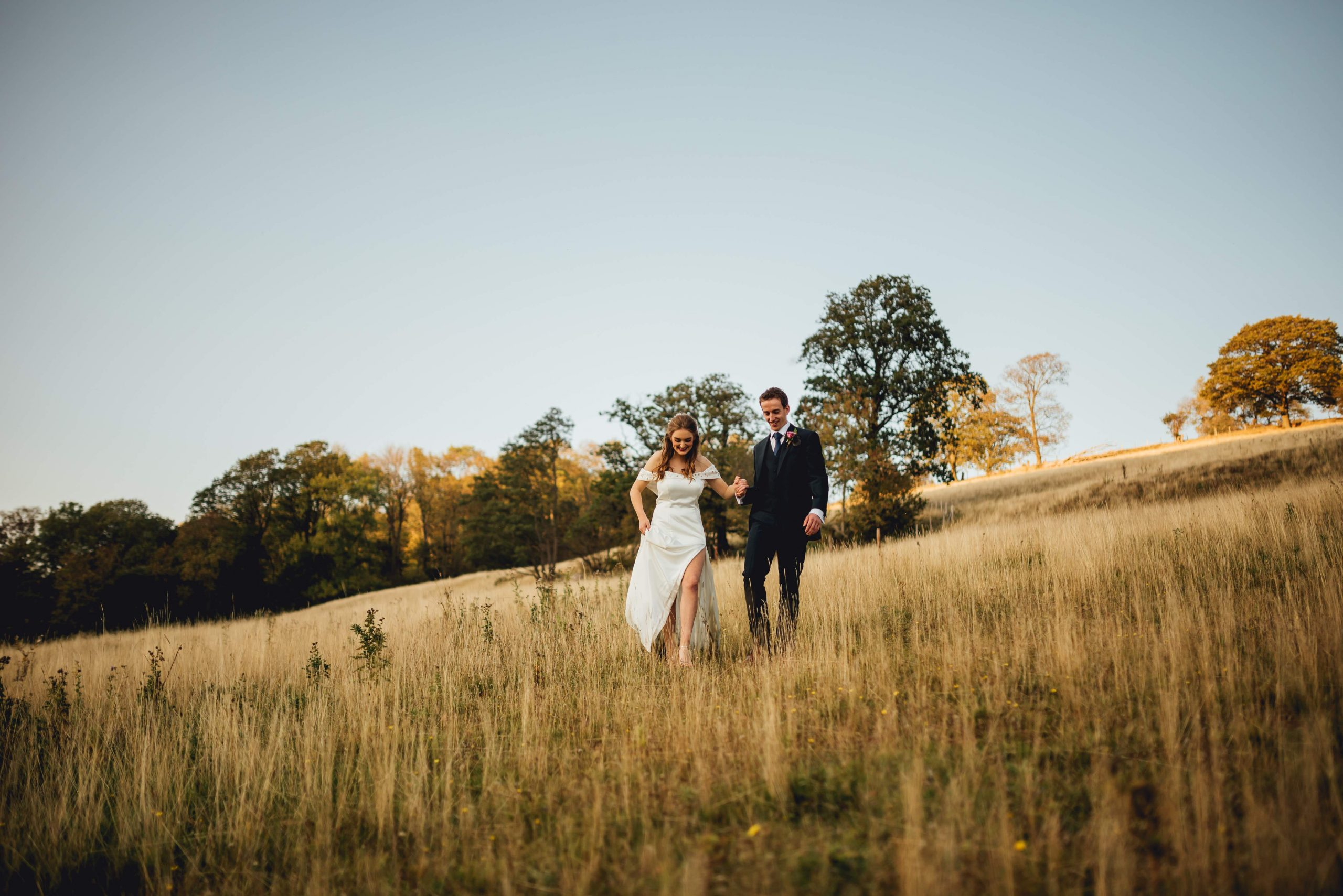 bride and groom walking in a country field